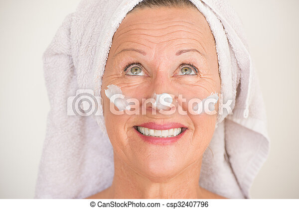 Portrait friendly attractive mature woman with towel and protective skin care creme and moisturiser lotion on happy smiling face, bright background.