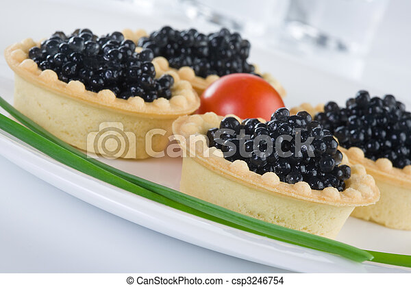 Tartlet with black caviar on a white platter - csp3246754