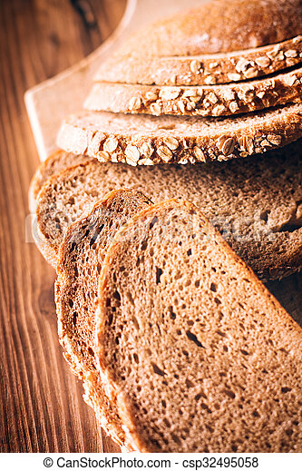 Brown bread on an old wooden table - csp32495058