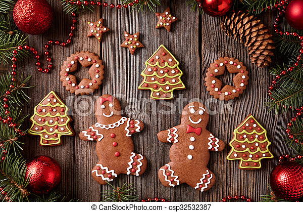 Gingerbread man and woman, fir trees, stars, christmas cookies composition with xmas tree decoration on vintage wooden table background. Homemade traditional new year dessert food recipe.