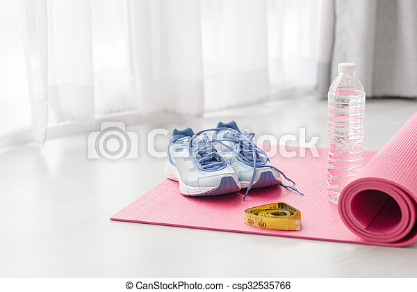 Sport shoes, yoga mat, bottle of water and centimeter on wooden background. Sport equipment. Concept healthy life. Selective focus