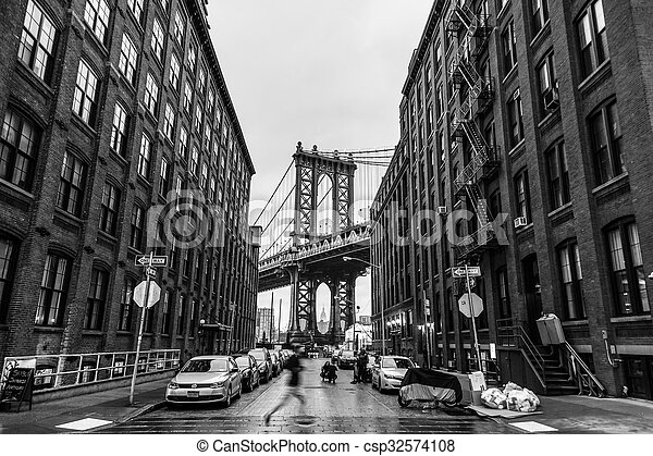 Manhattan Bridgeas seen from Washington street in Brooklyn, New York City, USA. Motion blured jogger running in foreground. Black and white image.