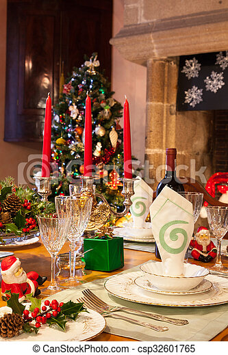 Elegant festive Christmas dinner table setting in warm light with a decorated tree, table decorations, dinnerware and glassware in a French country house - vertical format