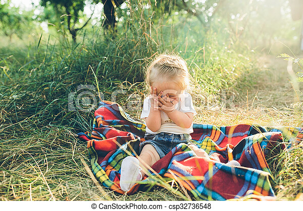 little girl sitting on the lawn - csp32736548