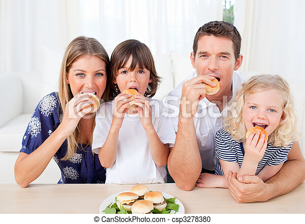 Hungry family eating burgers in the living room - csp3278380