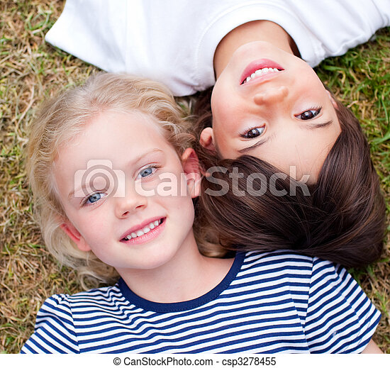 Close-up of cute siblings lying on the grass - csp3278455