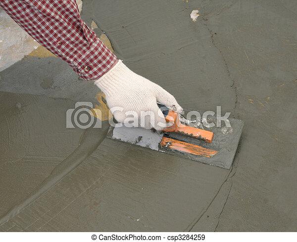 Hand with trowel spreading wet concrete - csp3284259