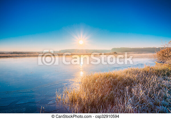 Sun rises over the river. Autumn frost frozen river covered with