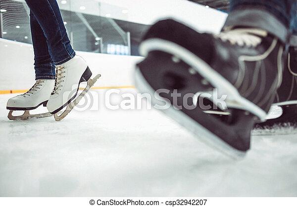 Man\'s hockey skates and women\'s figure skates on ice background