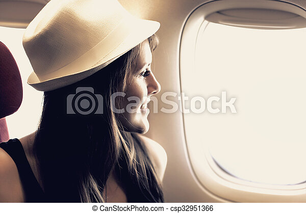 Young woman is looking through a window in the aircraft