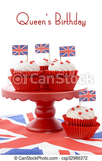 Red white and blue theme cupcakes on red cake stand with UK Union Jack flags on white wood table with Queens Birthday sample text.