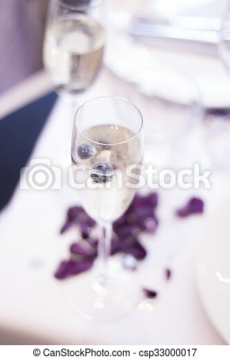 Champagne sparkling white wine glass flute on table with rose petals in restaurant bar in wedding reception party photo.