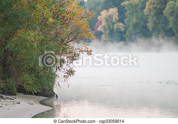 fog on an autumn river with green forest - csp33059014