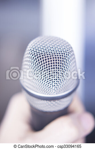 Audio recording vocal studio professional microphone to record singing or voice-overs held in hand of man.