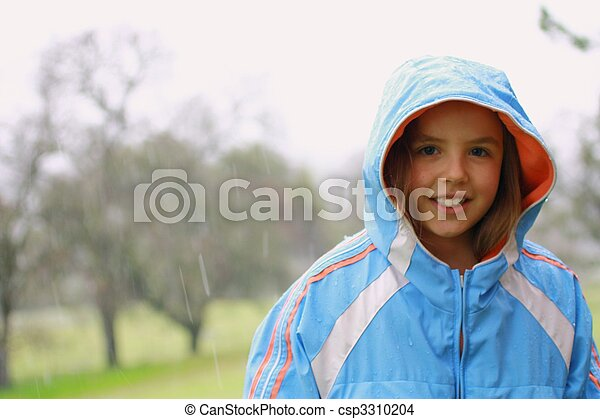 Young cute girl in the rain with blue rain coat.