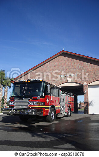 Red and black fire engine parked in front of Fire Station number 3. Image is vertical and shows truck front and driver side as well as the front of the fire station.