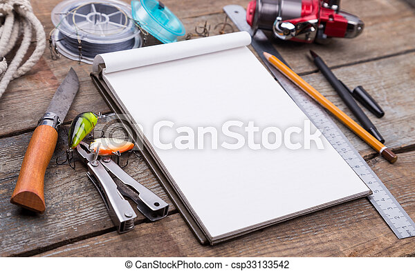 white writing-book with fishing tackles and design tools on wooden board. for mockup, print, design.