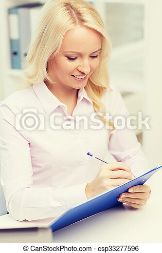 smiling businesswoman with clipboard in office - csp33277596