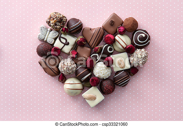 Chocolate candies and dried rose flowers heart shape composition. Sweet gift of love for St. Valentines Day.