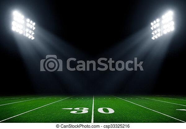 American football field at night with stadium lights