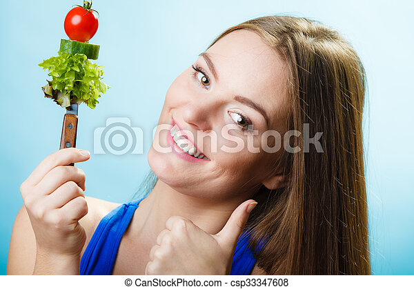Dieting weight loss concept. Sporty girl fitness woman holding knife with fresh mixed vegetables making thumb up hand gesture on blue background.