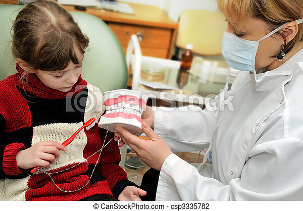 A little girl learning to clean a teeth at a dentist - csp3335782