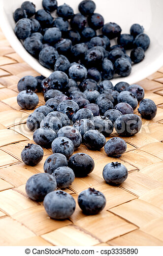 blueberries spilling from a bowl onto a placemat - csp3335890