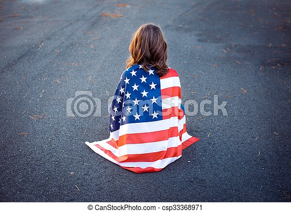 Sad lonely patriot woman sitting down with the american flag wrapped around her. Deployment, military life and relationship concept