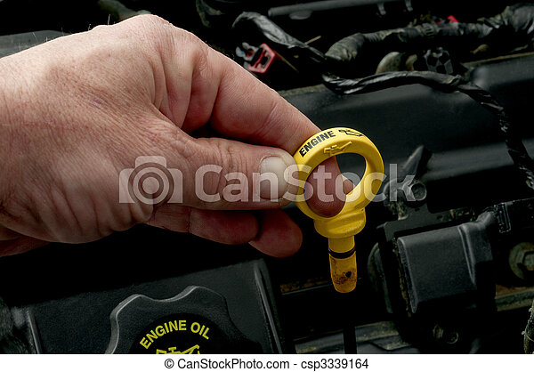A mans hand pulling the dipstick to check the motor oil level - csp3339164
