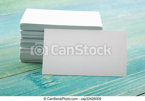 White blank business visit card, gift, ticket, pass on blue wooden background.