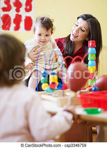 two little girls and female teacher in kindergarten - csp3346759