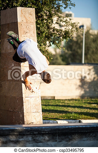Young athlete showing skills of free running. Parkour trick with city wall