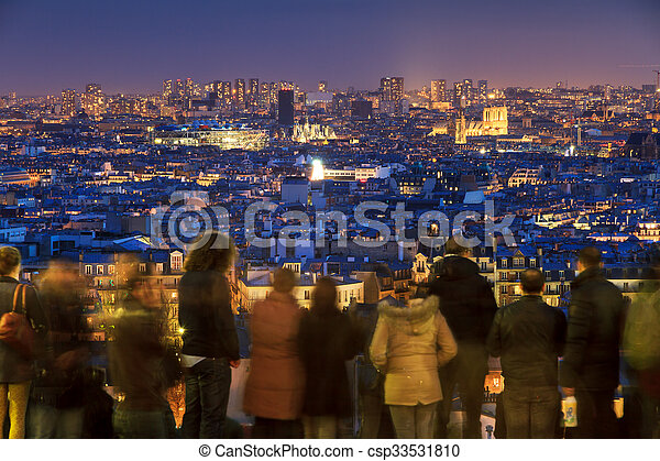 People looking at the beautiful skyline of Paris from Montmartre at night