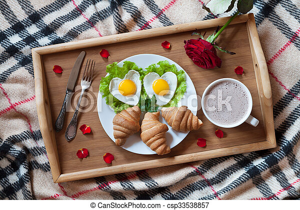 Romantic breakfast in bed with heart-shaped eggs on salad, croissants, coffee, rose flower and petals on wooden tray. Top view
