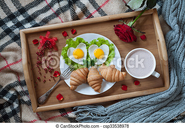 Delicious romantic breakfast in bed surprise with heart-shaped eggs, jam toasts, croissants, rose flower and petals on wooden tray table. Valentines day healthy meal concept.