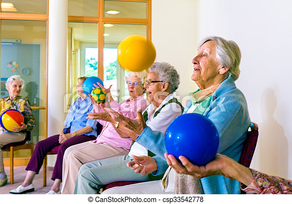 Group of happy senior ladies doing coordination exercises in a seniors gym sitting in chairs throwing and catching brightly colored balls