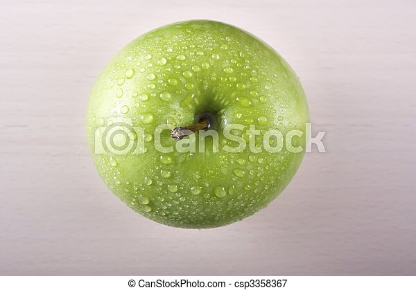 Fresh granny smith apple shot from directly above on board with water drops - csp3358367
