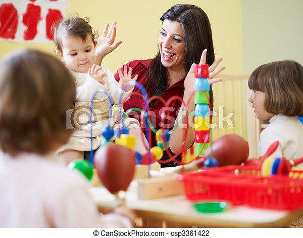 three little girls and female teacher in kindergarten - csp3361422