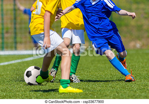 Young boys playing football soccer game. Running players in blue and yellow uniform. Final game of football tournament for kids.
