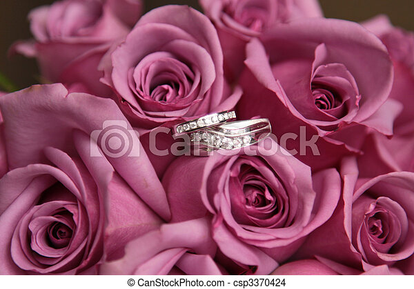 Wedding rings in a bouquet of pink roses.