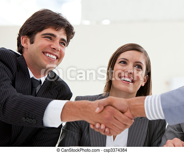 Smiling businessman and his colleague closing a deal with a partner in a meeting - csp3374384