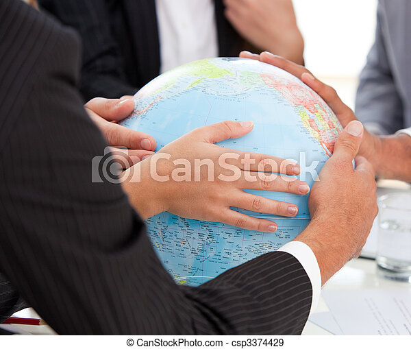 Close-up of a serious businessteam touching terrestrial globe - csp3374429