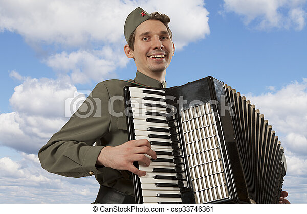 Soviet soldier in uniform of World War II playing the accordion on the blue sky background