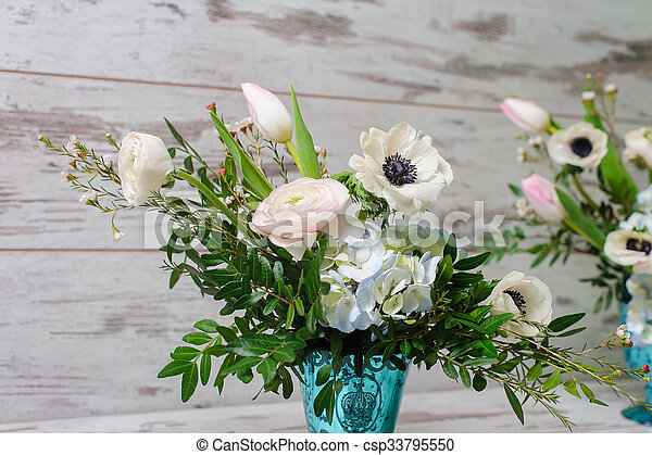 Two Bouquets of ranunculus, anemones and other fresh flowers in two blue vases stands on the background of vintage floor.