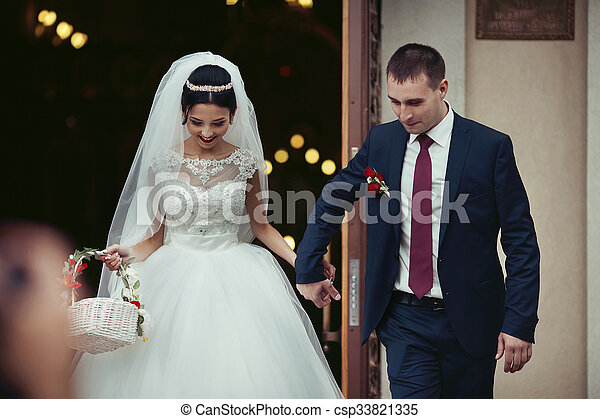 Happy newlywed romantic couple coming out of church after wedding ceremony with a candy basket - csp33821335