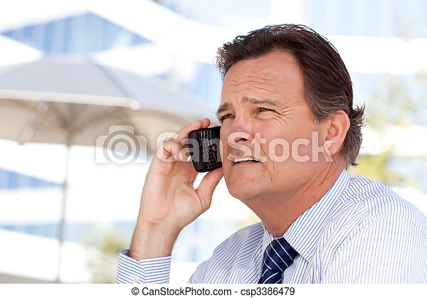 Businessman Smiles as He Talks on His Cell Phone - csp3386479