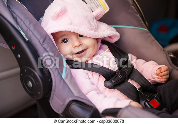Happy baby girl in a car seat