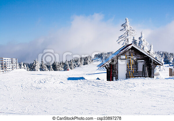 Vacation rural winter background with small wooden alpine house covered with snow, snow field, blue sky, copy space