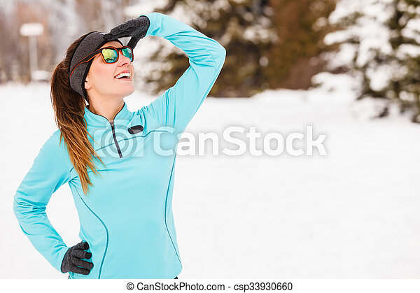 Sports and activities in winter time. Slim fit fitness woman outdoor. Athlete girl training wearing warm sporty clothes outside in cold snow weather.