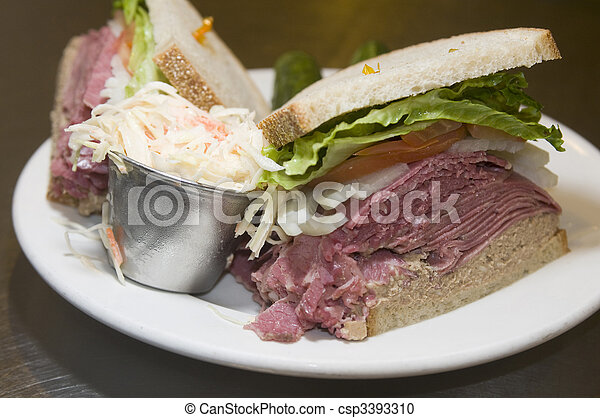 combination deli sandwich corned beef tongue chopped liver on rye bread with lettuce tomato onion and pickles at kosher delicatessen - csp3393310